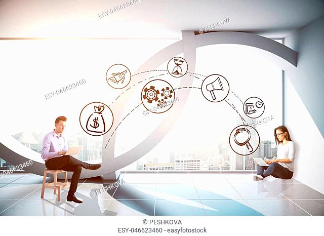 Businessman and woman using laptops connected with digital business icons in modern concrete interior with city view. Communication concept