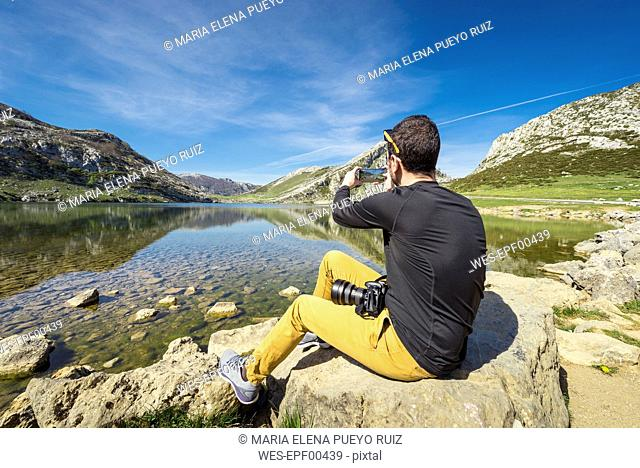 Spain, Asturias, Picos de Europa National Park, man taking picture at Lakes of Covadonga