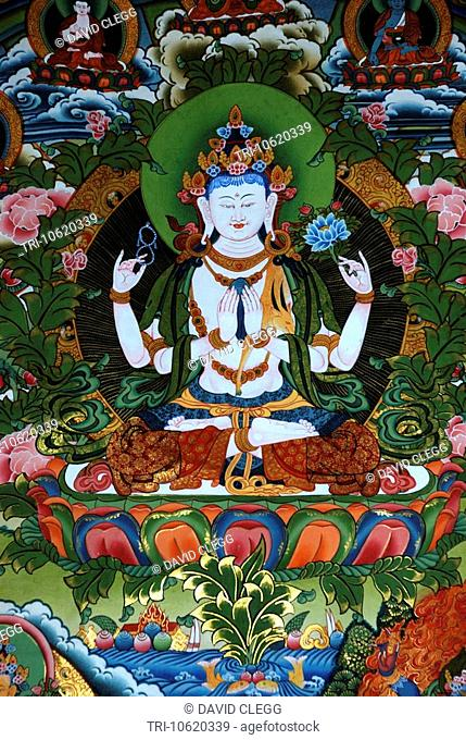 Colourful cloth print of a white four-armed Buddha seated on lotus flower and holding a lotus flower a double halo surrounds him Gelugpa Buddhist Association...