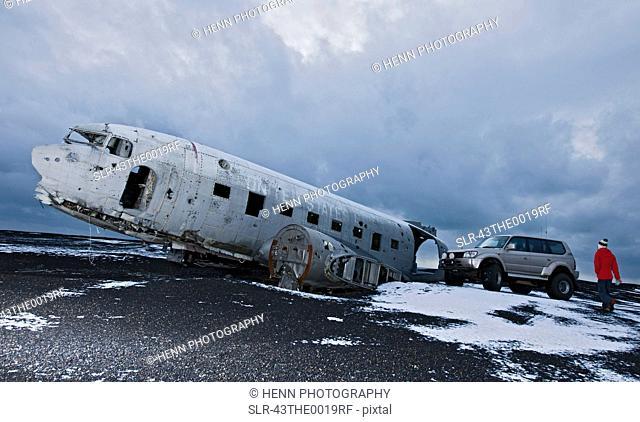 Hiker exploring airplane wreck in snow
