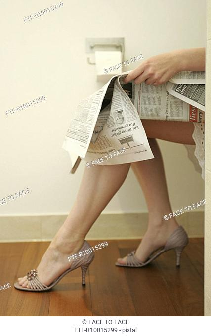 Legs of a woman seen as she sits on a water closet reading a newspaper