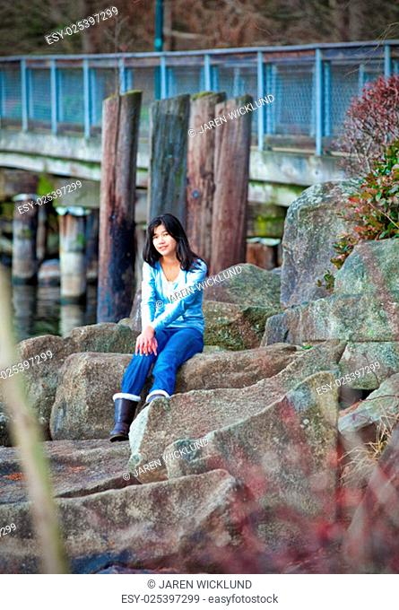 Young biracial teen girl in blue shirt and jeans sitting on large boulder along lake shore, relaxing. Earyl autumn or spring season