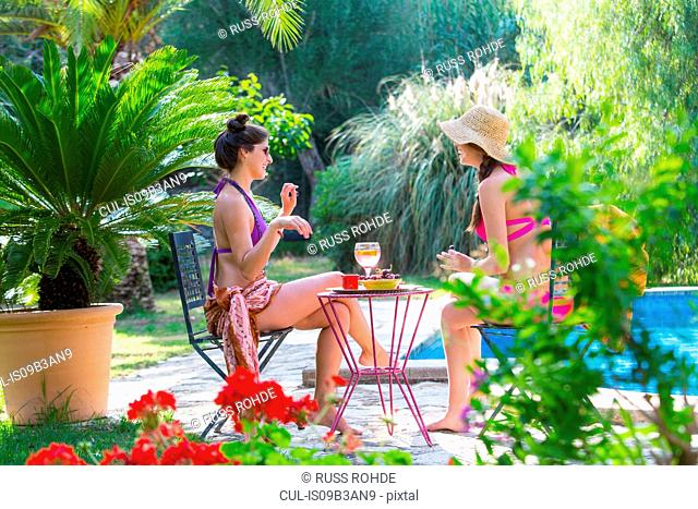Women poolside enjoying a drink