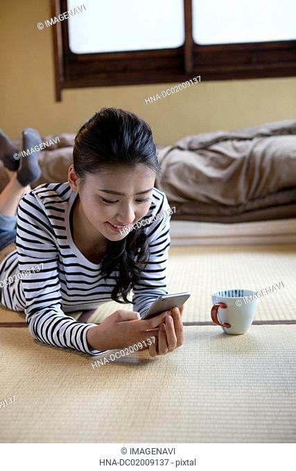 Young Japanese woman using smartphone on Tatami