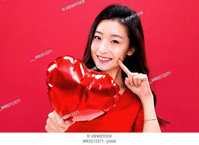 Young woman with a heart-shaped balloons