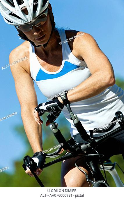 Female cyclist monitoring heart rate on wristwatch