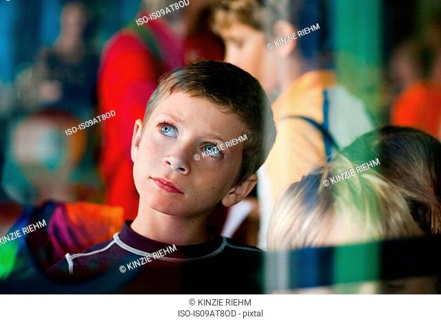 View through glass of young boy on outing looking up thoughtfully