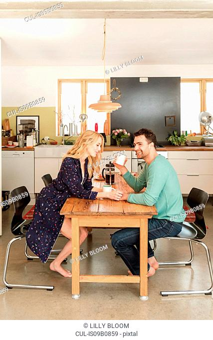 Couple at dining table drinking coffee