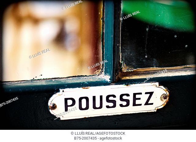 closeup of an old sign on a door that puts Poussez, Paris