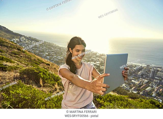 South Africa, Cape Town, Signal Hill, young woman above the city taking a selfie with tablet