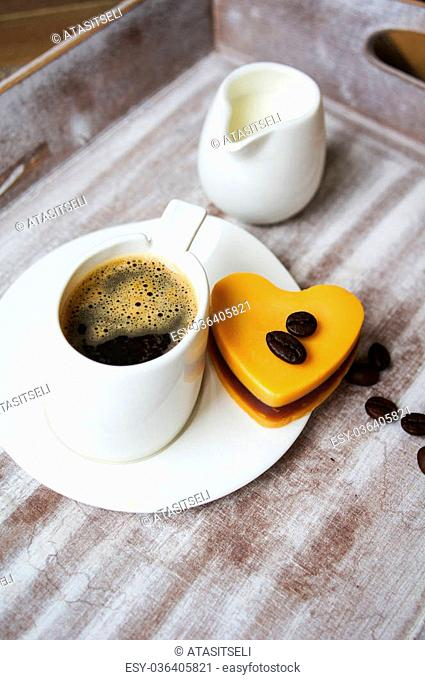 Heart shaped Mocca cake with cup of coffee and Valentine deocrations