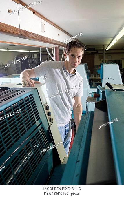 Portrait of a blue-collar man standing behind a printing machine