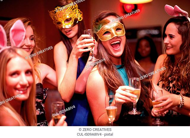 Young women with drinks wearing masks at hen party