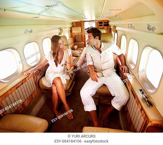Relaxed couple look into one anothers eyes in the cabin of a plane on vacation