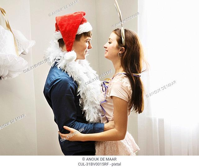 Couple embracing wearing christmashats