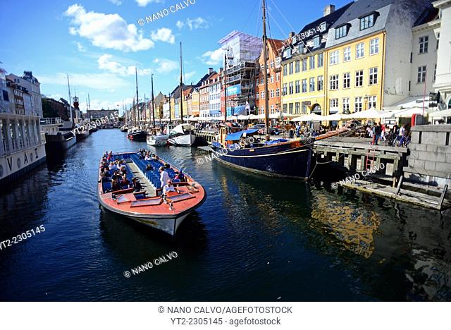 Touristic ferry in Nyhavn (literally: New Harbour), 17th-century waterfront, canal and entertainment district in Copenhagen, Denmark