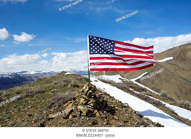 American flag waving from pile of rocks on mountain