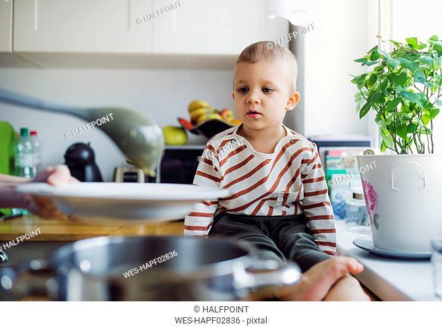 Toddler boy watching mother preparing food in kitchen at home