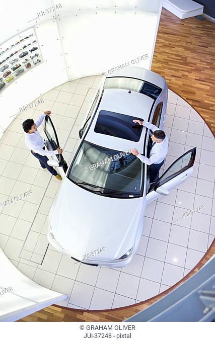 Salesman and customer looking at car in car dealership showroom