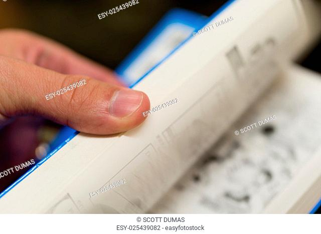 A close up of a hand flipping through the pages of a paperback book