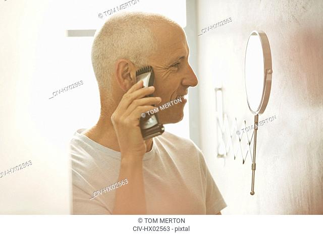 Mature man shaving with electric shaver at magnification mirror in bathroom