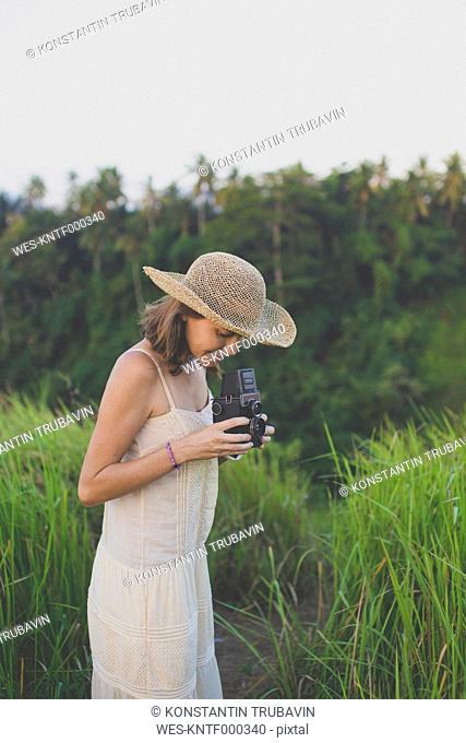 Smiling woman with retro camera in nature