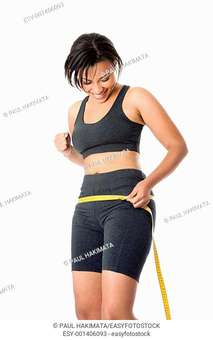 Beautiful happy toned woman weight conscious measuring her size shape around waist hips, celebrating her successful weightloss, dressed sporty in grey, isolated