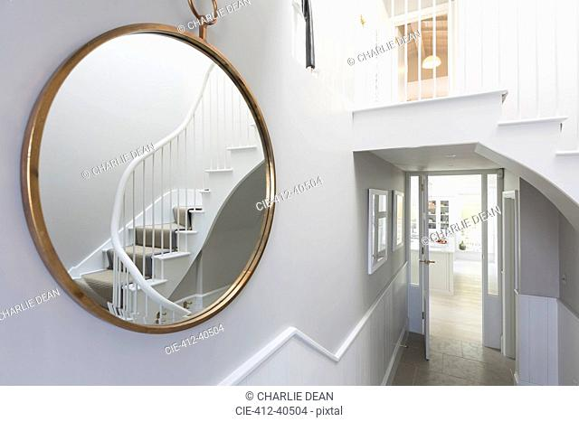 Reflection of foyer staircase in round mirror