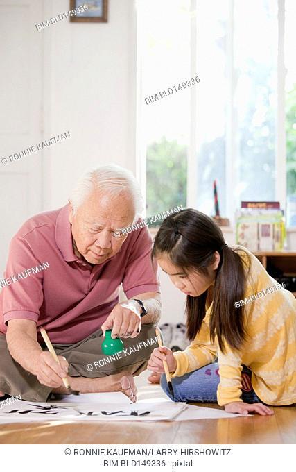 Japanese man teaching granddaughter calligraphy