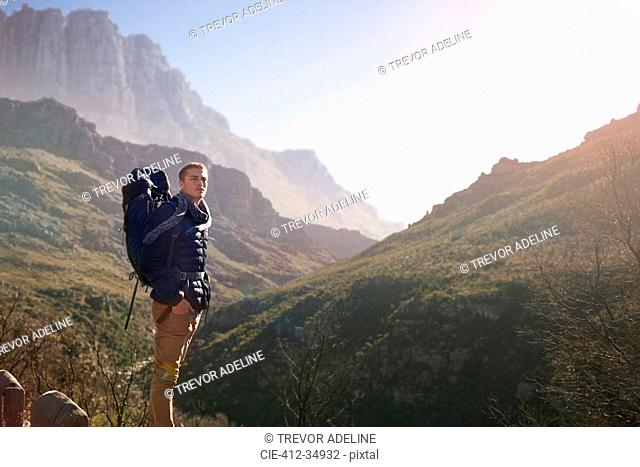Young man with backpack hiking, looking at sunny mountain view