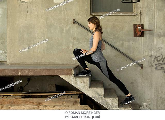 Young woman stretching leg on steps
