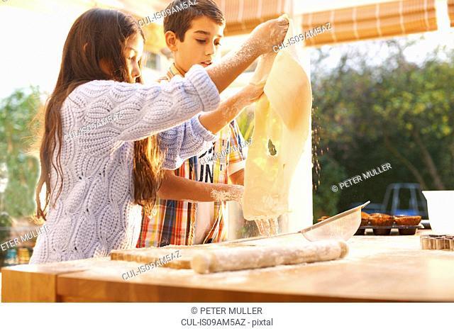 Children making dough in kitchen
