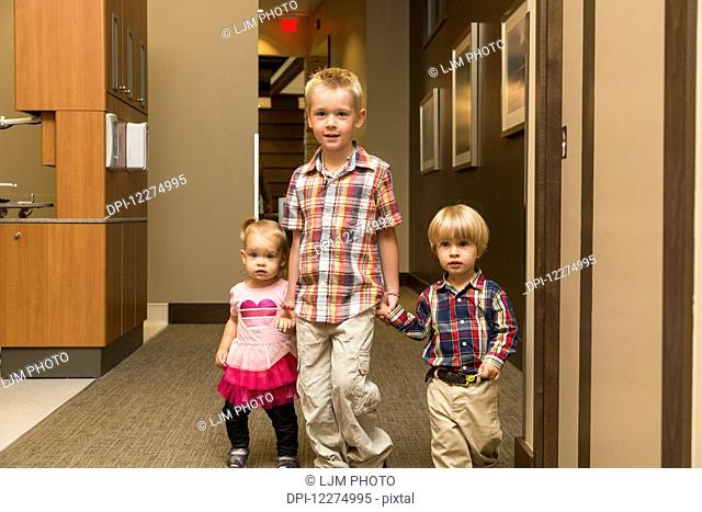 Three young children holding hands and walking down hallway in family dental clinic; Edmonton, Alberta, Canada