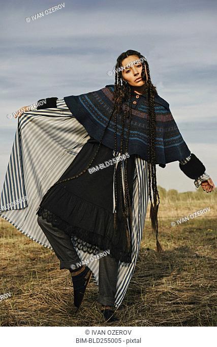 Caucasian woman wearing traditional clothing dancing in field