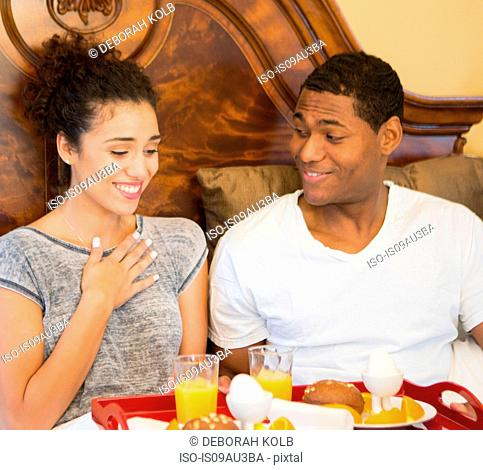 Mid adult man surprising young woman with breakfast in bed