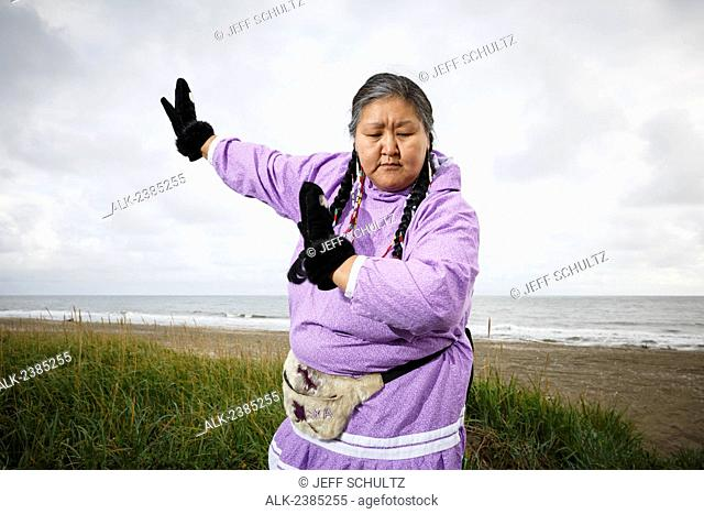 Portrait of Yupik Eskimo woman in kuspuk dancing outdoors Nome, Alaska, Summer
