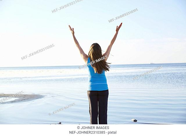 Woman standing with raised arms at seaside