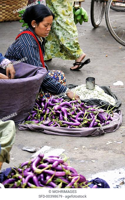 Woman selling aubergines at a market in Burma