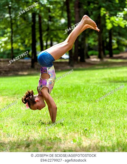 A 10 year old girl doing gymnastics in a park