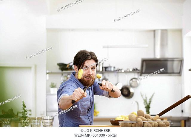 Man skewering potatoes in kitchen