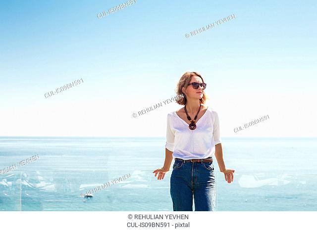 Woman leaning against glass balcony on seaside terrace
