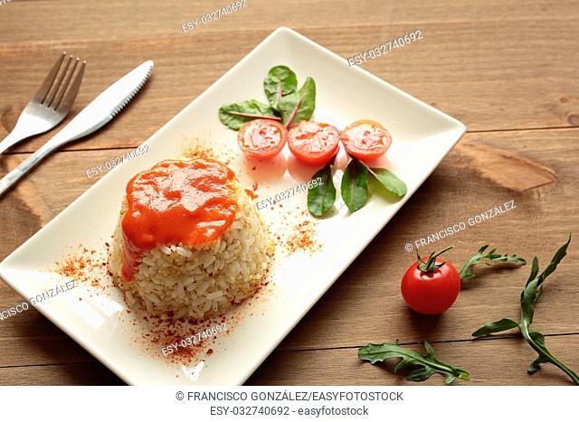Cuban style rice decorated with cherrys tomatoes and a green leaves