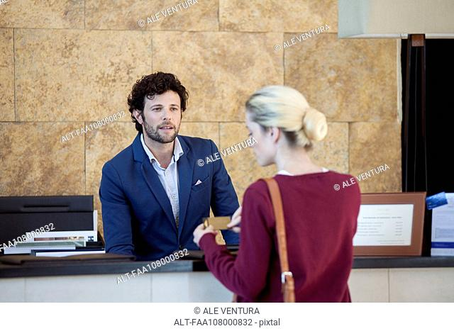 Hotel receptionist assisting guest