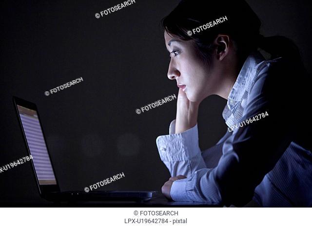 Businesswoman using laptop in the dark, Tokyo Prefecture, Japan