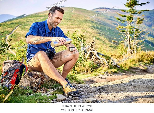 Smiling man resting during hiking trip pouring cold water from thermos flask