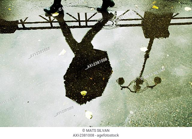 Reflection in a puddle of a person walking with an umbrella and a lamp post; Locarno, Ticino, Switzerland