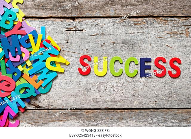 """The colorful words """"""""SUCCESS"""""""" made with wooden letters next to a pile of other letters over old wooden board"""