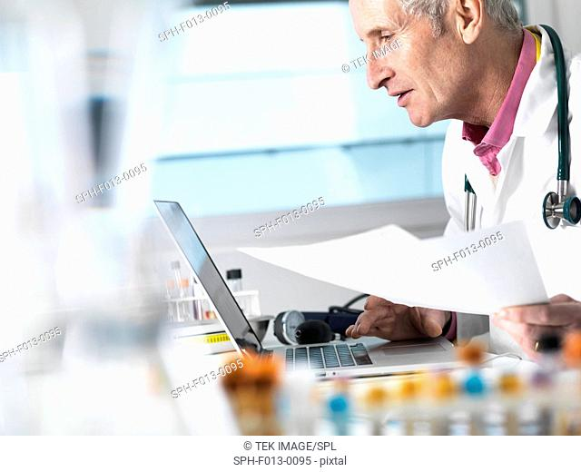 Doctor accessing patient records on laptop and medical paperwork