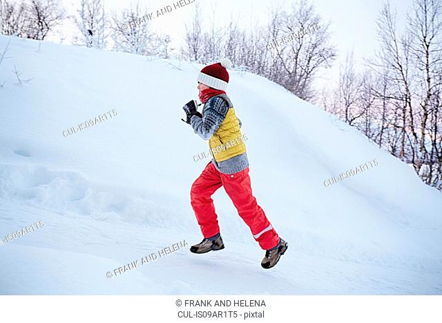 Boy running up snow covered hill, Hemavan,Sweden