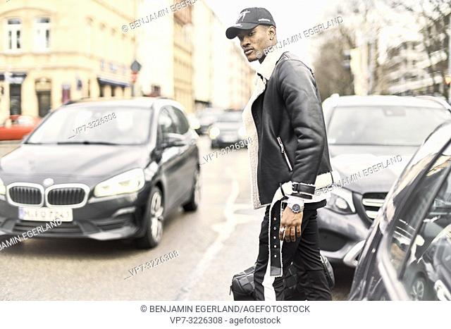 man, walking at street, between cars, streetstyle, in Munich, Germany
